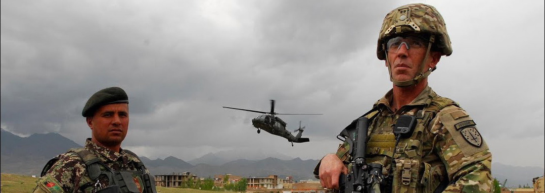 Header image- service members in foreground with helicopter and damaged buildings in background- 54th Security Force Assistance Brigade page