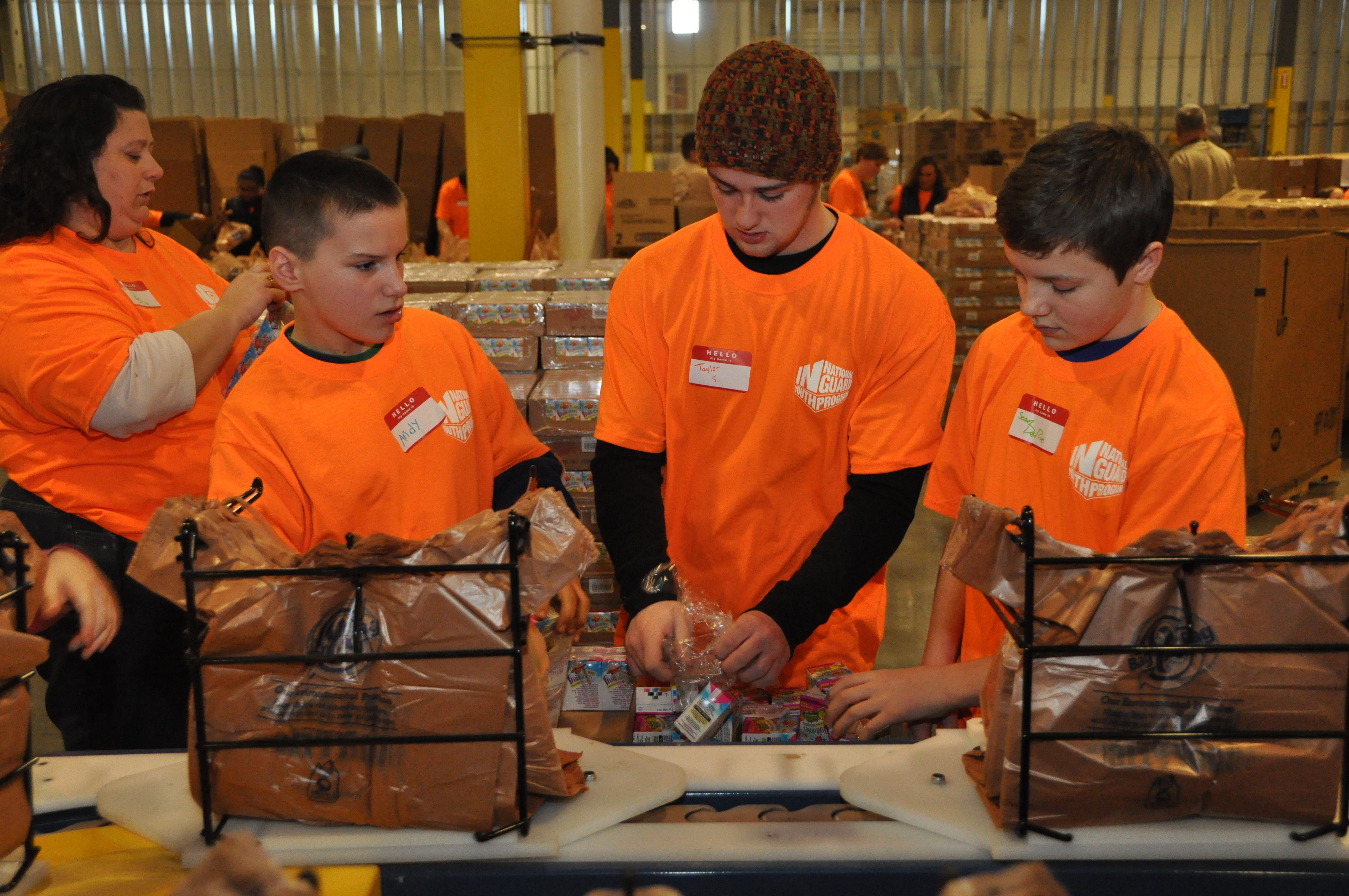 youth filling grocery sack for food drive